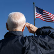 Older veteran saluting flag